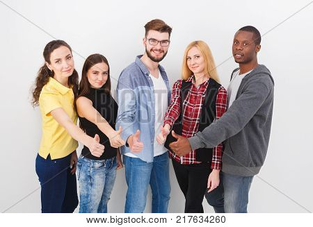 Multiethnic group of young adults showing thumbs up while standing on white background.