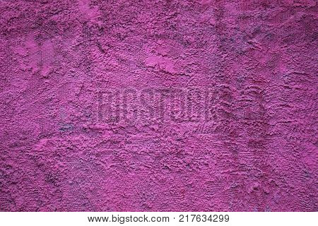Abstract background texture of a rough concrete wall bright purple color. The rough blank surface