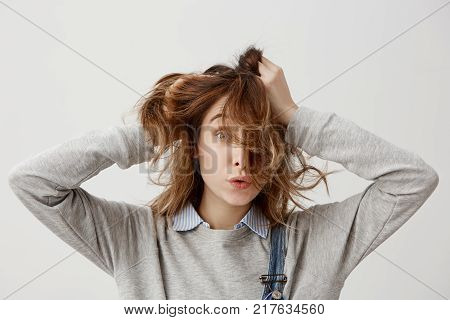 Portrait of funny girl touching her beautiful auburn hair while spending day-off at home being alone. Brunette woman in casual posing on camera with pleasant facial expressions. Close-up