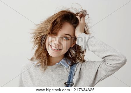 Headshot of lucky young lady touching her head with hand looking on camera with broad smile. Good-looking housewife being surprised after winning in lottery. Unexpectedness, rejoice