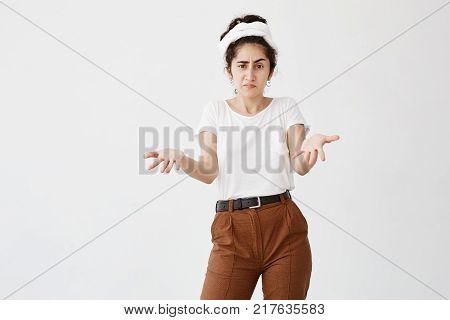 It's not a big deal. Clueless young dark-haired woman dressed in white t-shirt and brown trousers, pursuing up lips, shrugging shoulders, staring at camera with anger after she did something wrong but not feeling sorry or guilty at all