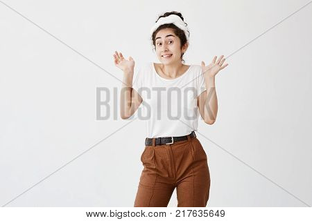Indoor portrait of emotional clueless young dark-haired female wearing white t-shirt and brown trousers, shrugging shoulders, standing with open palms, expressing indifference, uncertainty, disregard or disinterest. So what, Who cares.