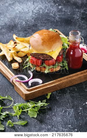 Homemade traditional hamburger with beef, tomato, cheese, aragula, served on wooden slate serving board with french fries and ketchup sauce on dark texture background.