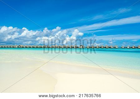 Wooden villas over water of the Indian Ocean Maldives. Beautiful tropical landscape with sandy beach and Indian ocean.