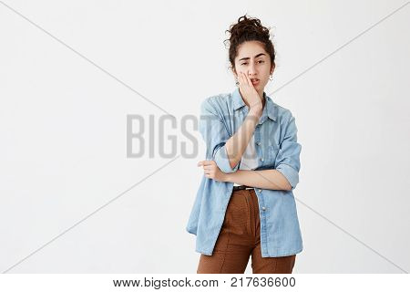 Isolated portrait of troubled young woman with dark hair in bun in denim shirt touching her chin and looking sideways with doubtful and sceptical expression, making important life decision, frowning face