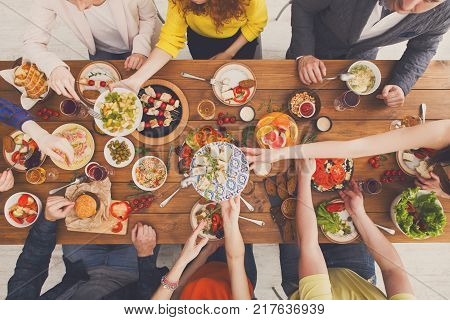 People eat healthy meals at festive table served for party. Friends celebrate with organic food on wooden table top view. Company having lunch, passing burrito.