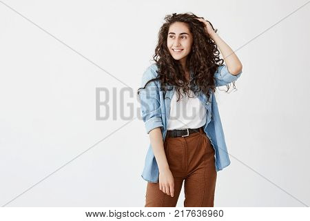 Horizontal portrait of beautiful good looking girl with appealing appearance smiles happily, wears her long wavy hair loose, has good mood after spending weekends with friends, glad and pleased to pose at camera