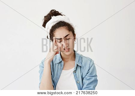 Indoor picture of dark-haired pensive female model in white do-rag with closed eyes keeps hand on temple, suffers from headache after being worried, feels badly. Negative emotions and face expression.