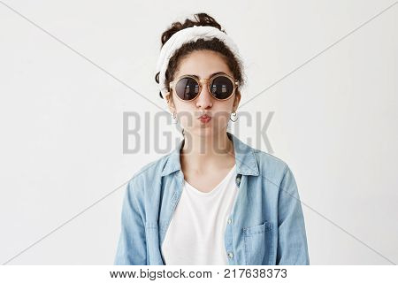 Funny female model with dark hair in bun pouts lips, in denim shirt and roung sunglasses, makes grimace as stands in studio. Joyful pretty woman has fun indoors, blows cheeks, foolishes at camera