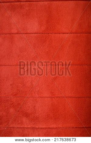 Red texture of fluffy carpet with horizontal stripes background.