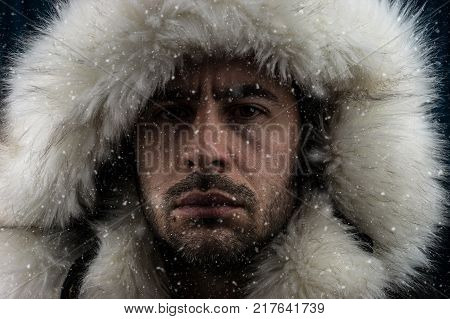 Close up portrait of a white man dressed with an eskimo jacket in the snow looking at the camera