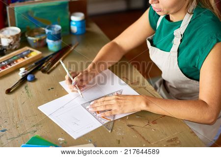 High angle of  young woman drafting sketch with pencil for art and craft project sitting at wooden table in workshop