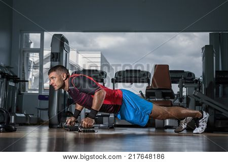 Fitness training. Man doing push ups exercise using Push-up Bars in  gym