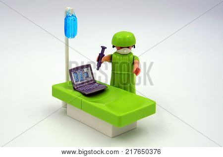 Amsterdam, The Netherlands-  December 10, 2017: Playmobil doctor injecting antivirus in a vires infected computer.