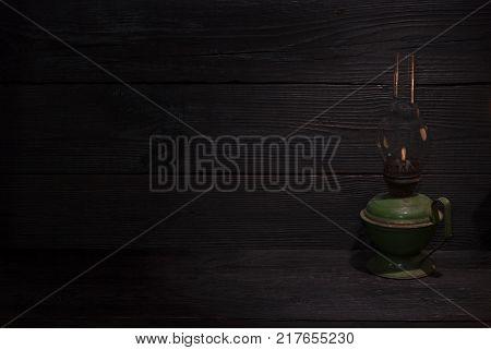 old kerosene lamp on a dark wooden background
