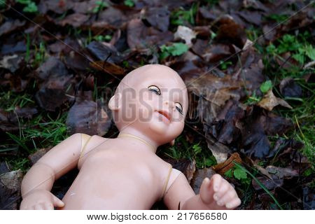 abandoned baby doll in the grassr on the road concept for sad emotion thriller departed