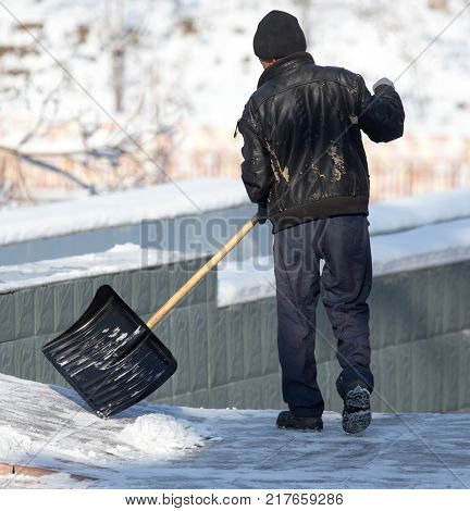Worker cleans snow shovel in the nature .