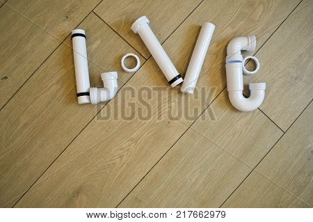 The word love is laid out of plumbing plumbing white plastic pipes fittings flanges and gaskets on the background of beige boards. The text of the pipes. Inscription made of plastic pipes.