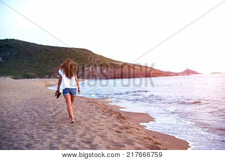 Young woman walk on an empty wild beach towards celestial beams of light falling from the sky. poster