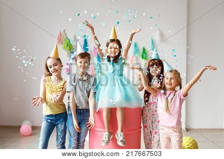 Adorable kids have fun together, throw colourful confetti, wears cone hats, have fun at birthday party, play together in different games, spend time in decorated room. Children and events concept