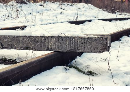 Snowbound rails. Concrete block lying on the rail and blocking the way.