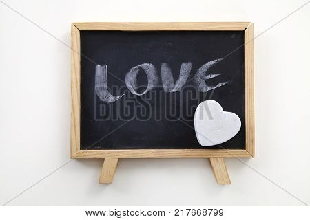 heart shaped white eraser on blackboard with the word LOVE