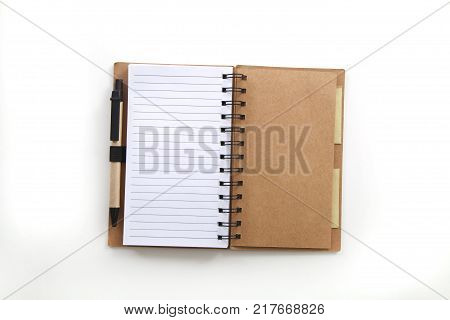 open spiral notebook with raws paper and a pen