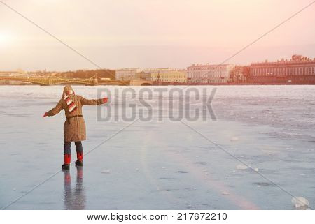 Young teen girl cautiously goes on the slippery ice to the middle of the river. In the background decorated for Christmas bridge and St. Petersburg embankment.