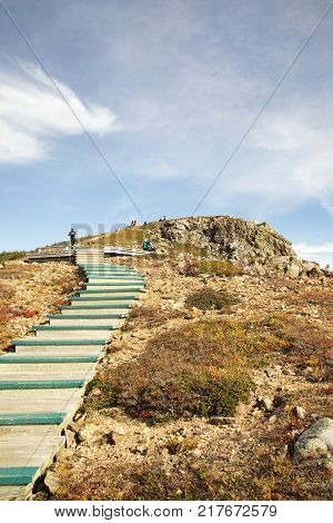 Cape Breton Highlands National Park Nova Scotia Canada - October 29 2017 : Tourists on wooden steps and boardwalk on French Mountain in Cape Breton Highlands National Park Nova Scotia Canada.