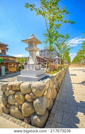 Stone lantern on Dankazura the pathway flanked by cherry trees that from Tsurugaoka Hachiman sanctuary leads to beach of Kamakura, Japan. Wakamiya-oji street offers spectacular landscapes in spring. poster