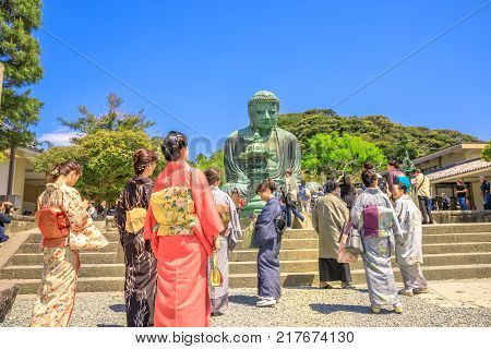 Kamakura, Japan - April 23, 2017: Japanese women in traditional kimono looking Great Buddha or Daibutsu. The monumental Buddha Vairocana in Kotoku-in Temple is one of main attractions in Kamakura.