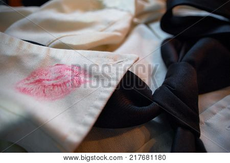 A lipstick stain on the collar of a men's dress shirt.