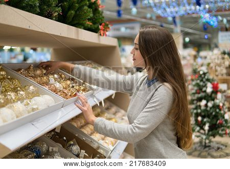 Beautiful happy customer girl choosing gifts for Christmas and New Year. She is taking Christmas tree decorations. Big supermarket sale during New year