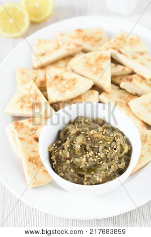 Homemade roasted eggplant dip or spread baba ganoush in the Mediterranean cuisine with olive oil and sesame on top homemade sesame pita chips on the side photographed with natural light (Selective Focus Focus in the middle of the dip)