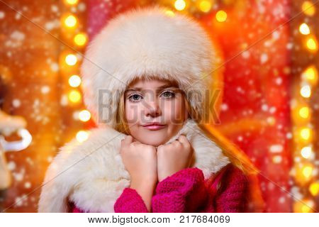 Portrait of a beautiful nine-year-old girl in a fur hat and scarf near her house decorated for Christmas.