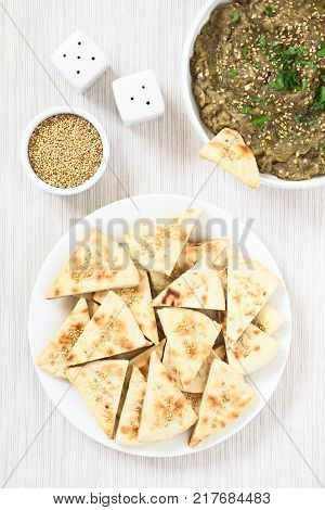 Homemade sesame pita chips with roasted eggplant dip or spread baba ganoush in the Mediterranean cuisine on the side photographed overhead with natural light