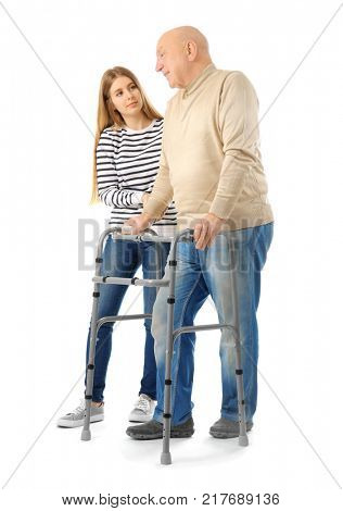 Young woman and her elderly grandfather with walking frame on white background
