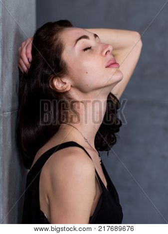 Side view portrait of beautiful young woman with brown hair standing against wall with her eyes closed pleasure expression on her face.