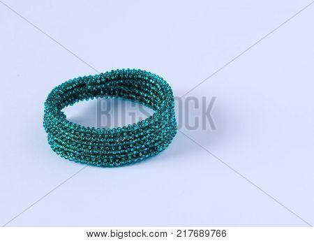Green bracelet on white background. The bracelet lies on paper