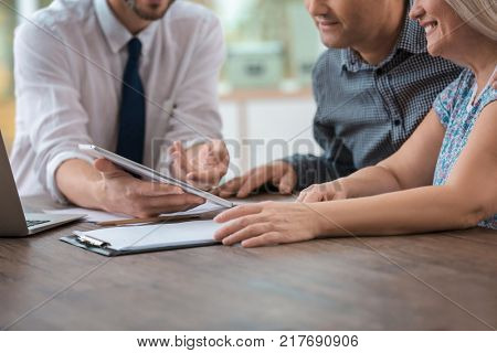 Male insurance agent consulting clients in office