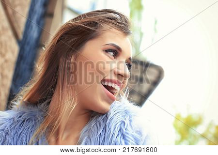 Attractive smiling woman in faux fur vest outdoors