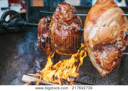 Large chunks of delicious pork hams cooked on an open fire. The street food. Food outdoors. Camping and cooking on a spit over the fire. Camping.