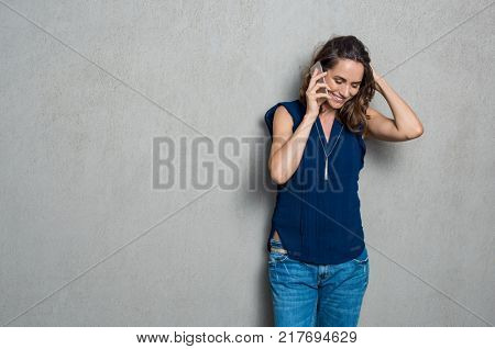 Mature woman talking on cellphone isolated over grey background with copy space. Cheerful hispanic woman in happy conversation on mobile phone. Beautiful latin woman talking on smartphone.