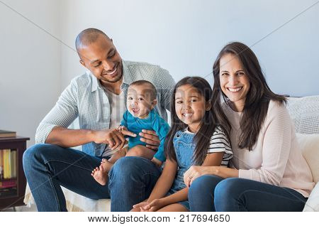 Portrait of happy multiethnic family sitting at home. Smiling couple with kids sitting on couch and looking at camera. Black father and latin woman with daughter sitting on couch and having fun.