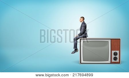 A small businessman sits in side view on a giant retro TV set with blank screen. Technologies in business. Obsolete approaches. Advertisement and promotion.