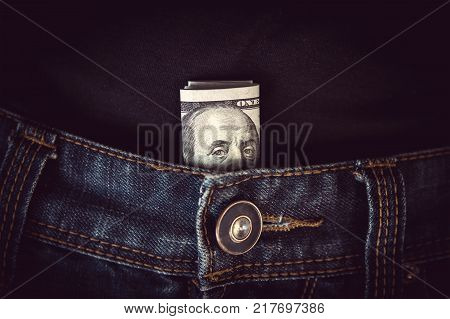 100 dollar bill sticking out from a blue jean pocket. pocket expenses. Benjamin Franklin looks out of the pants