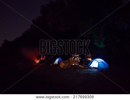 Night campground summer camp on the banks of the river