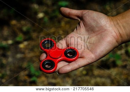 Red fidget spinner in a female hand