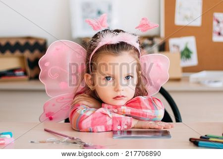 upset cute girl wait for art lesson. creative space. education for talented little ones.