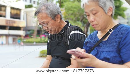 Asian senior couple use of cellphone together